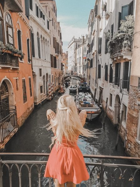 Blonde Girl standing on the edge of a canal in Venice