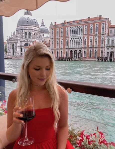 Samantha drinking a glass of red wine with BASILICA DI SANTA MARIA DELLA SALUTE in the background