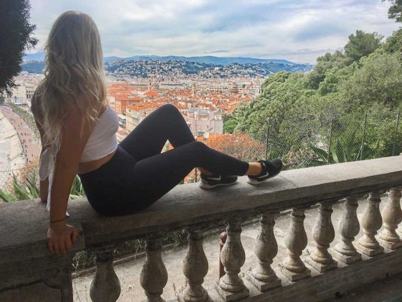 blonde girl sitting on a railing overlooking nice in one day