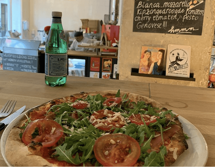 Pizza with arugula and tomatoes