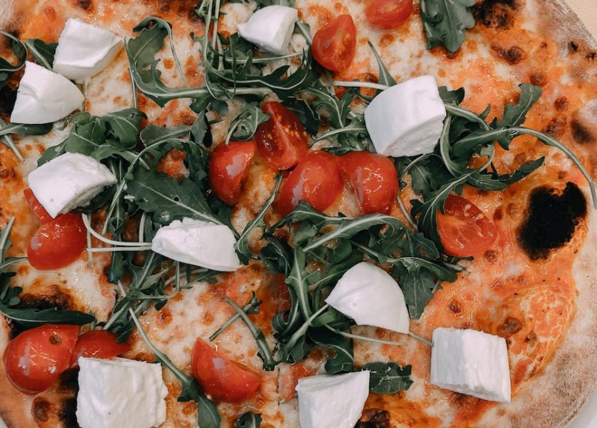 Pizza with mozzarella, tomatoes and arugula, eating one of the best things in Capri