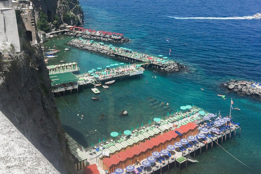 Things to do in Sorrento: Colourful sun-beds on top of benches built within the blue Sorrento waters