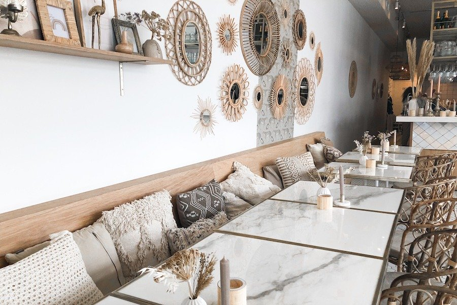 White marble table tops with a bench with pillows and beachy mirror accents