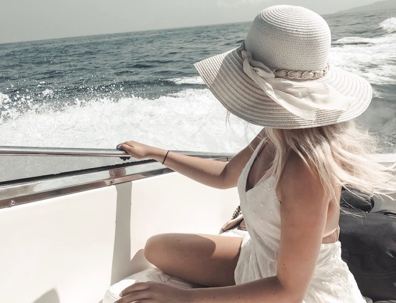 Blonde girl sitting on a boat in a white dress and white hat