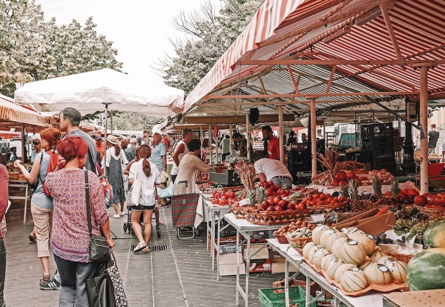 Street market full of fruit stands and people