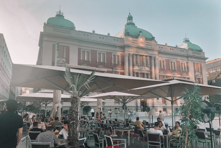 Red building with green top in the distance and cafe with umbrellas in the foreground