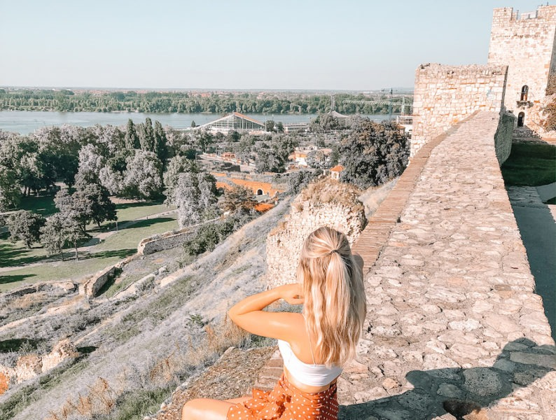 Blonde girl sitting on the edge of a stone fortress with city in the distance