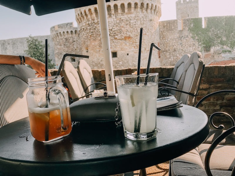 Two drinks on a table with the Belgrade fortress in the distance