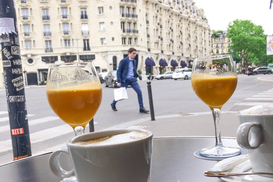Two glasses of orange juice and coffee with Parisian building in background