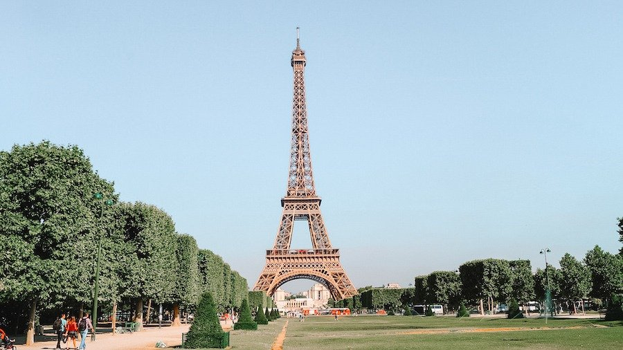 View of the Eiffel tower with lush grass in front and trees along the sides - one weekend in Paris