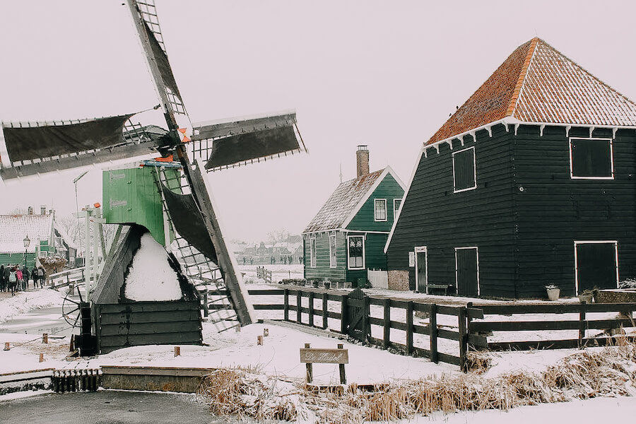 Green windmill covered in snow