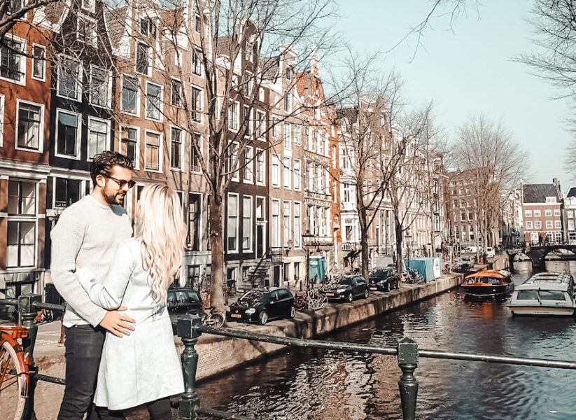 Two people standing along a canal in Amsterdam