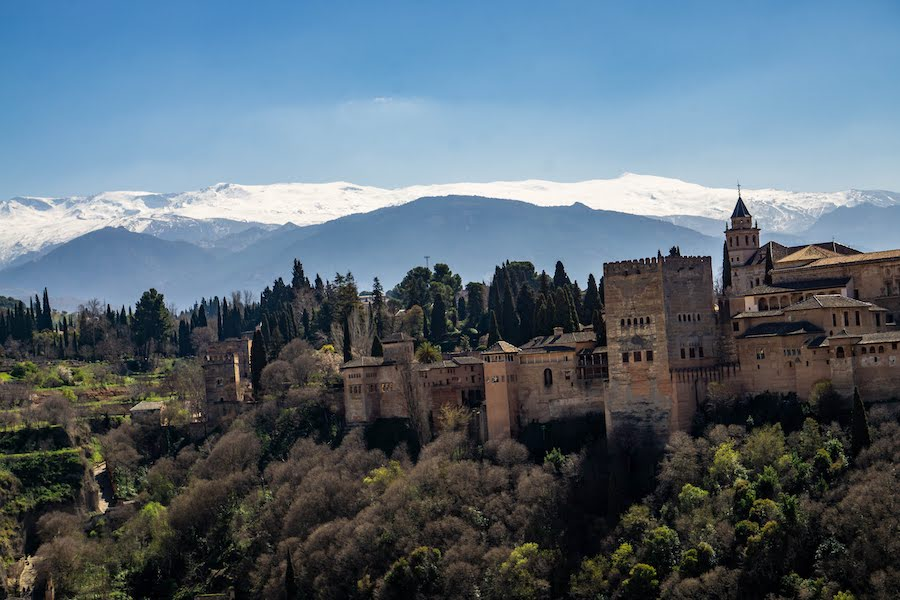 Castle on a mountain with snow capped mountains in the distance
