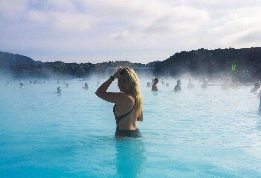 Blonde girl standing in the blue waters of the Blue Lagoon with people swimming in the disance
