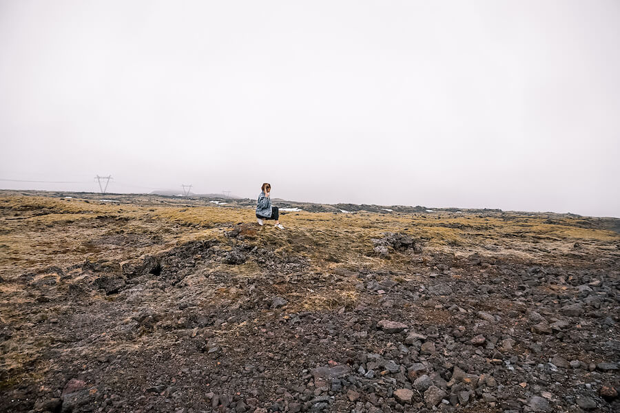 Blonde girl standing on rock formating in Iceland