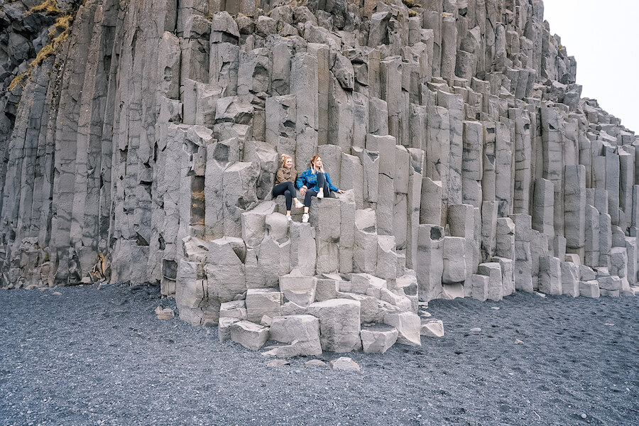 Two girls sitting on the basalt columns