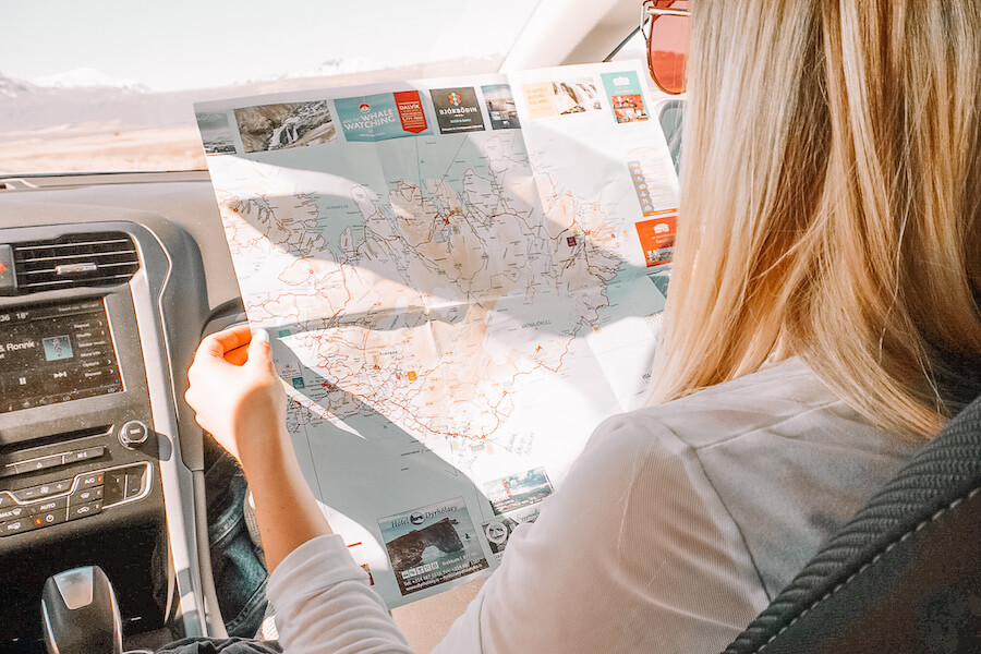 Blonde girl sitting in the front of a car looking at a map of Iceland