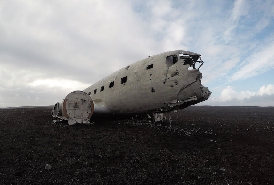 White shell of a plane sitting in the black sands with nothing in the distance