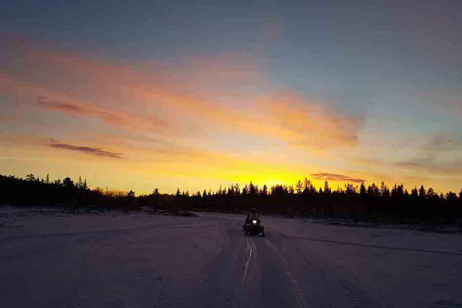 Snowmobile driving with orange lights in the distance