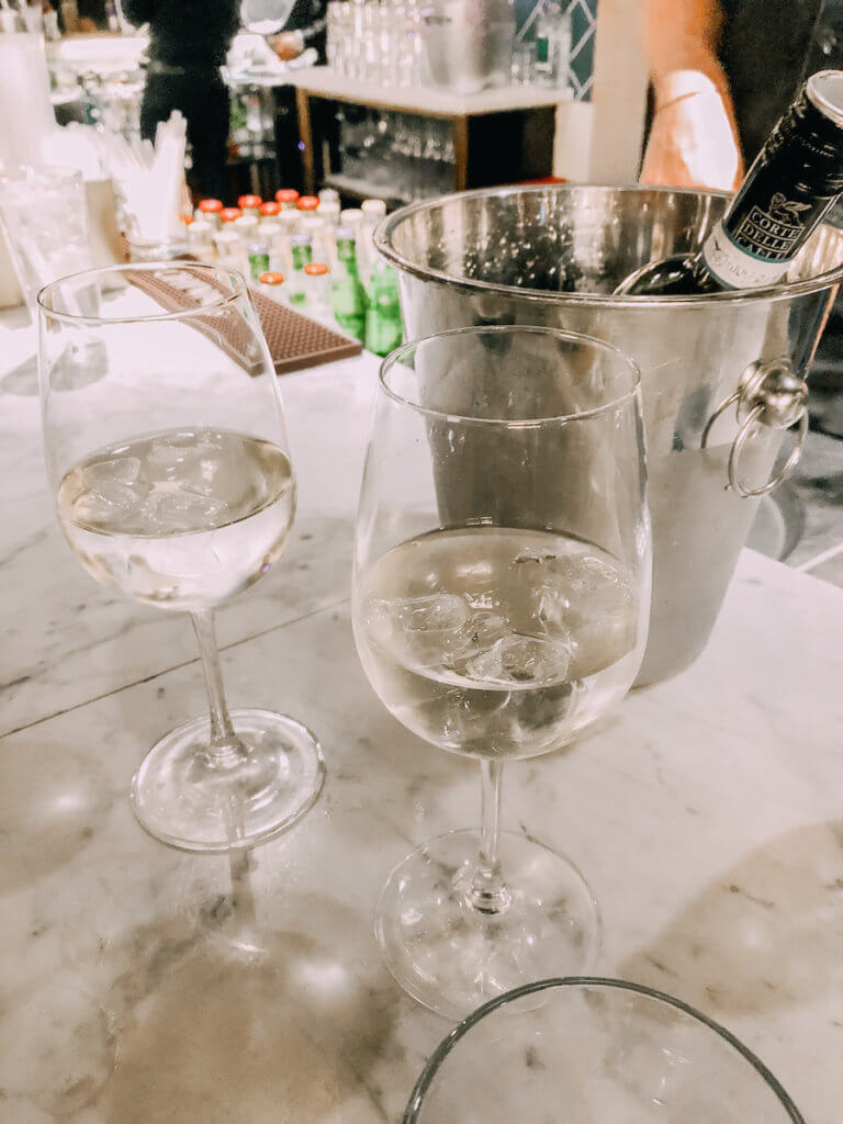 Two glasses of white wine on a bar counter