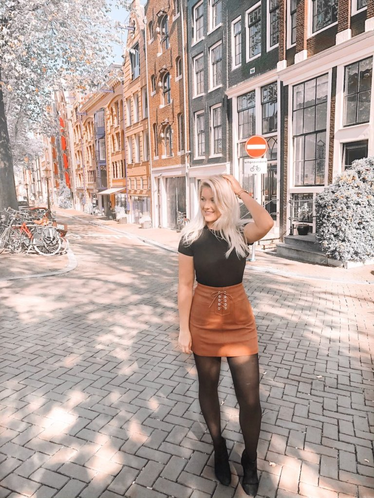 Blonde girl standing in one of the best photo spots in Amsterdam with the authentic houses in the distance