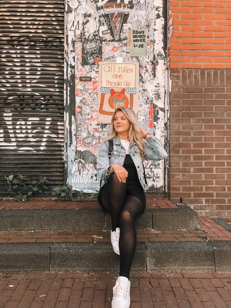 Girl sitting on a set of stairs with a door covered in art behind her