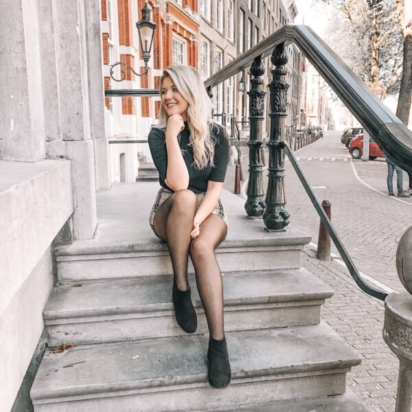 Blonde girl sitting on a white staircase with the city street and buildings behind her