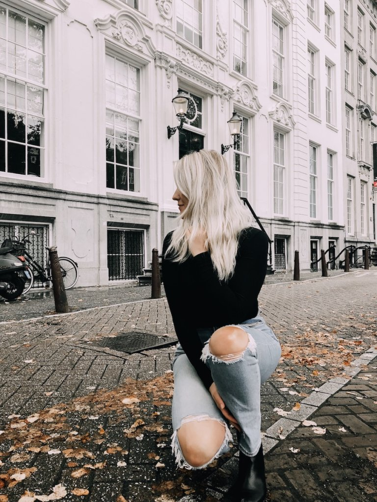 Girl kneeling on the road in front of a white building in Amsterdam