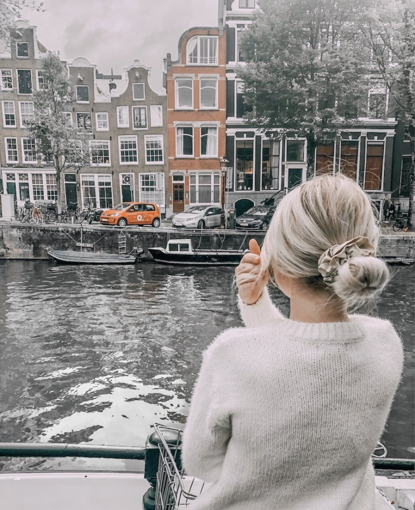 Girl standing backwards facing the canal and orange houses of Amsterdam
