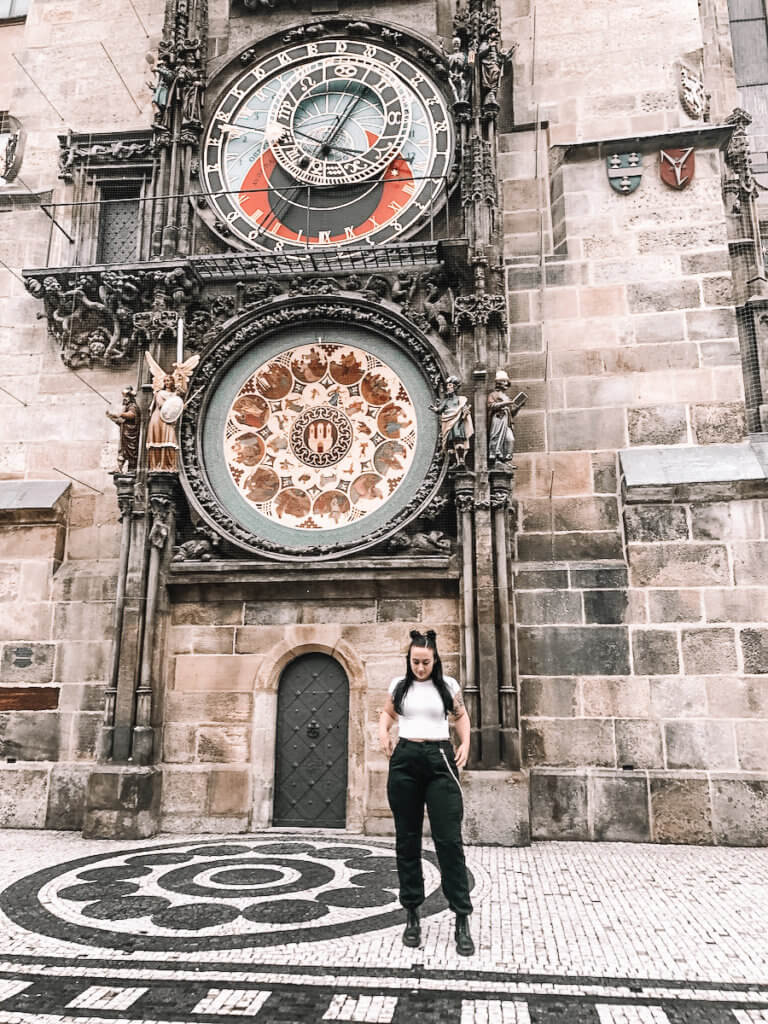 Brunette standing in front of a huge clock with various details