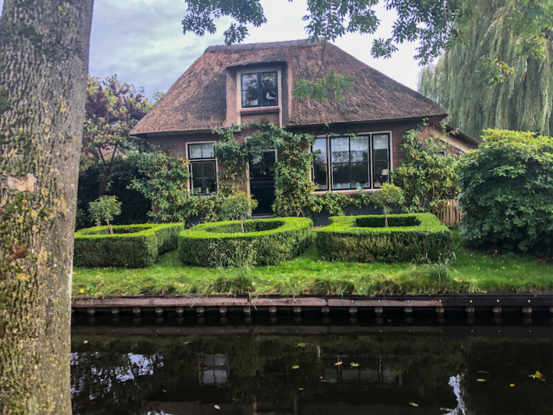 Thatched roof houses with greenery in front of it and a canal in front of that