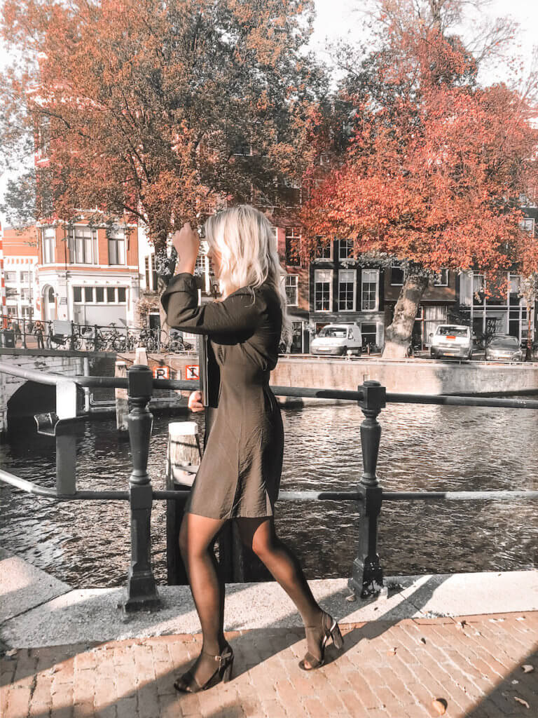 Blonde girl walking sideways infront of the canals in Amsterdam