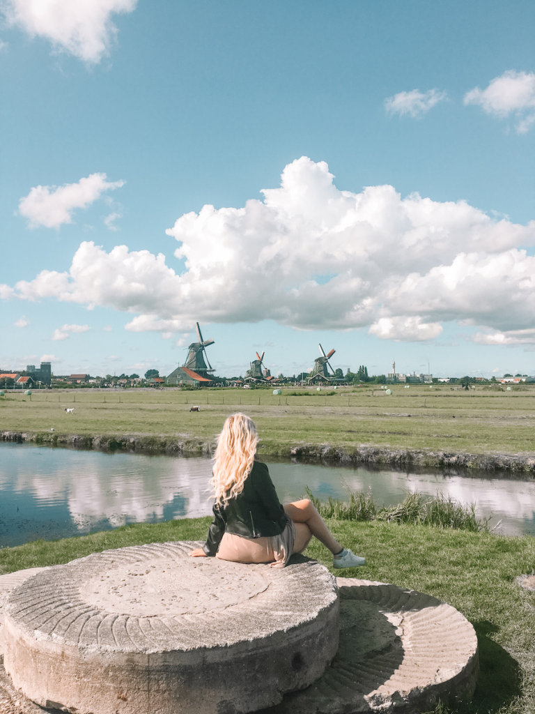 Girl sitting with three green coloured dutch windmills in the background