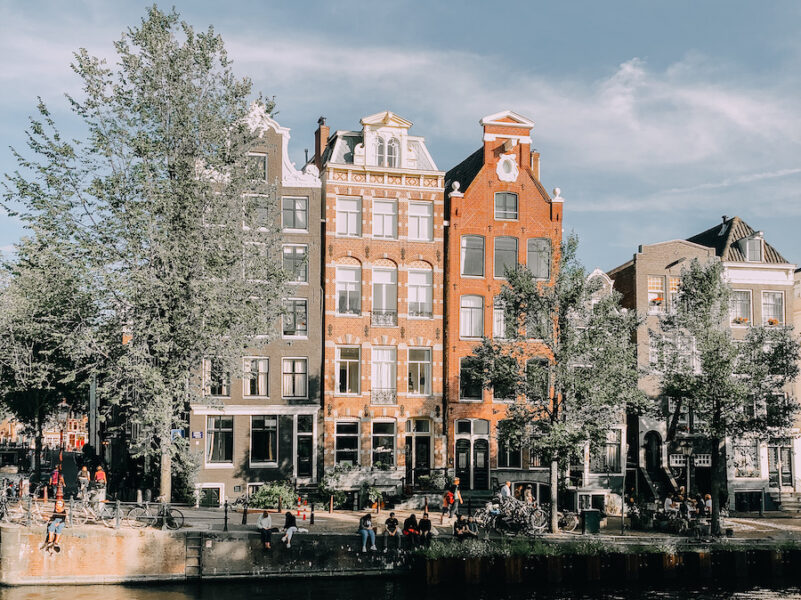 Orange hued houses in Amsterdam along a canal