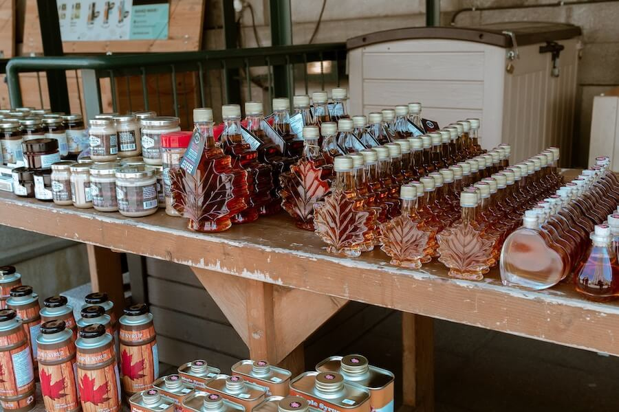 Maple syrup in glass bottles shaped like a maple leaf