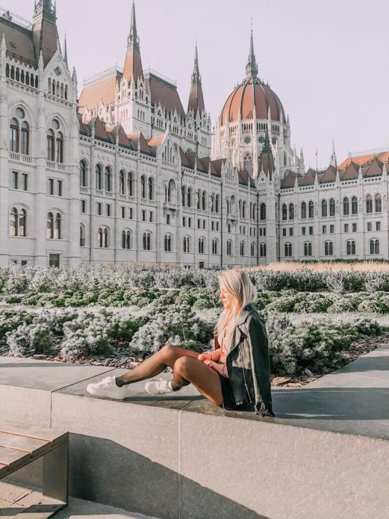 Girl sitting in front of the Hungarian Parliament