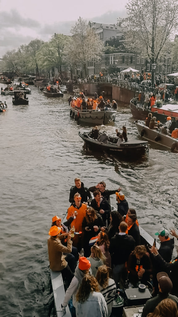 Boats in the canal in Amsterdam on Kingsday