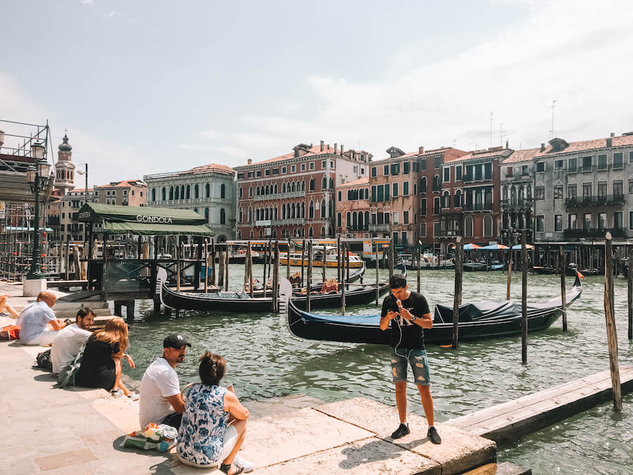 People sitting on the edge of the Grand Canal in Venice