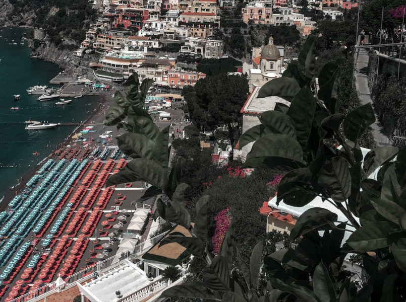 Upward view of he umbrellas on the beach in Positano with the buildings in the distance