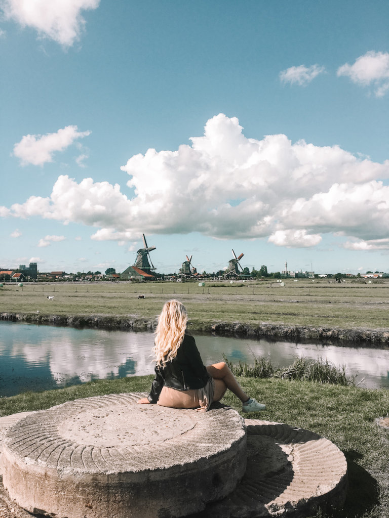 Girl sitting with dutch windmills in the distance