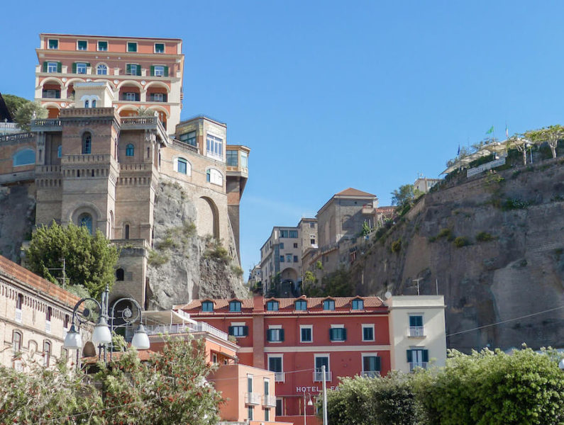Tall pink houses built into the cliffs in Sorrento