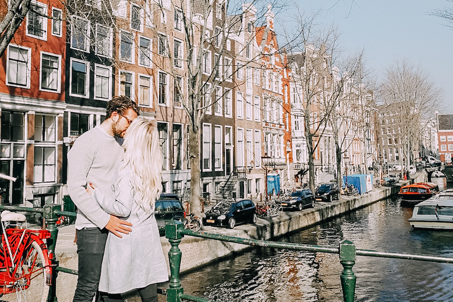 Couple kissing on a bridge in Amsterdam one of the top 10 romantic destinations in Europe