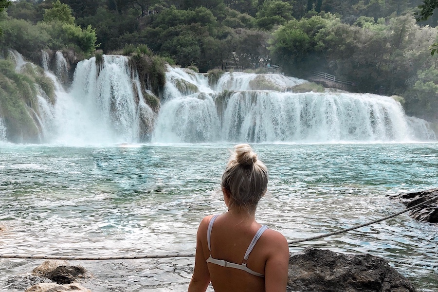 Girl sitting in front of the Krka waterfalls at an idyllic balkan holiday destination