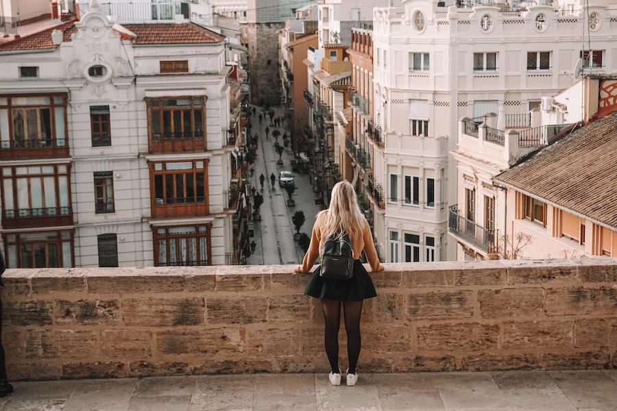 Girl standing at the ledge of Torres De Serrans overlooking the city