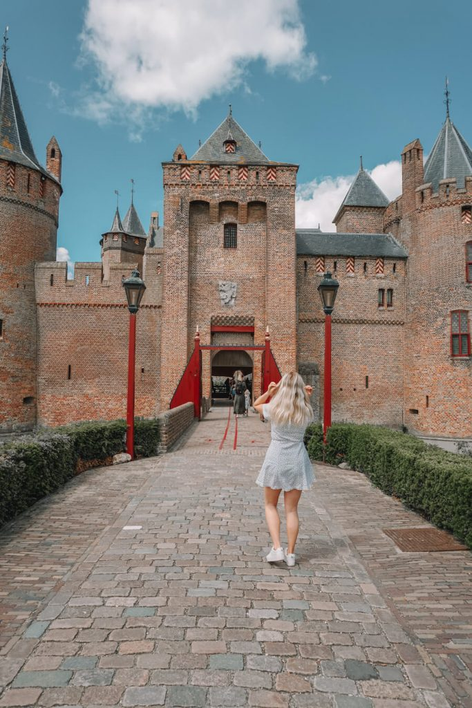 Girl walking into the gates of a castle