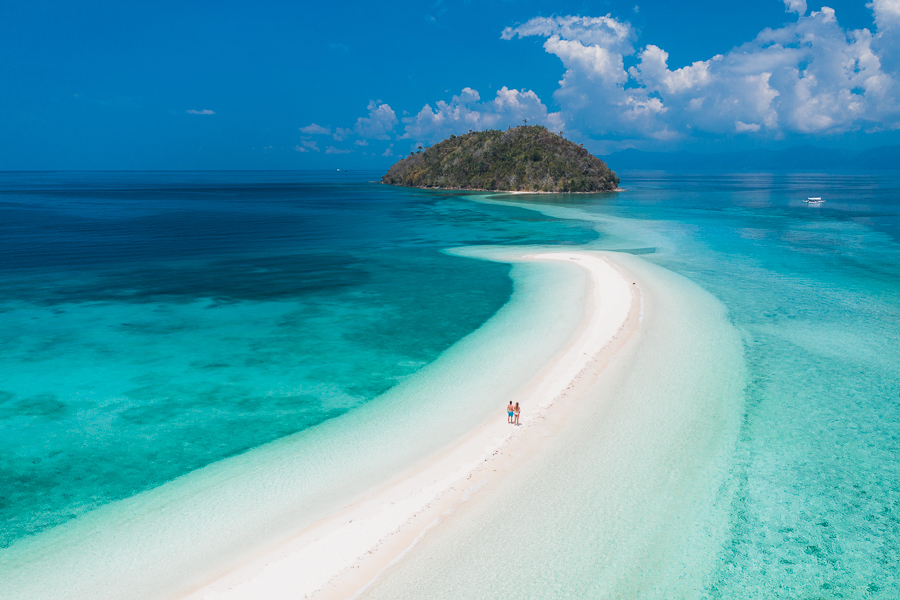 White sand beach in the middle of the vivid blue ocean
