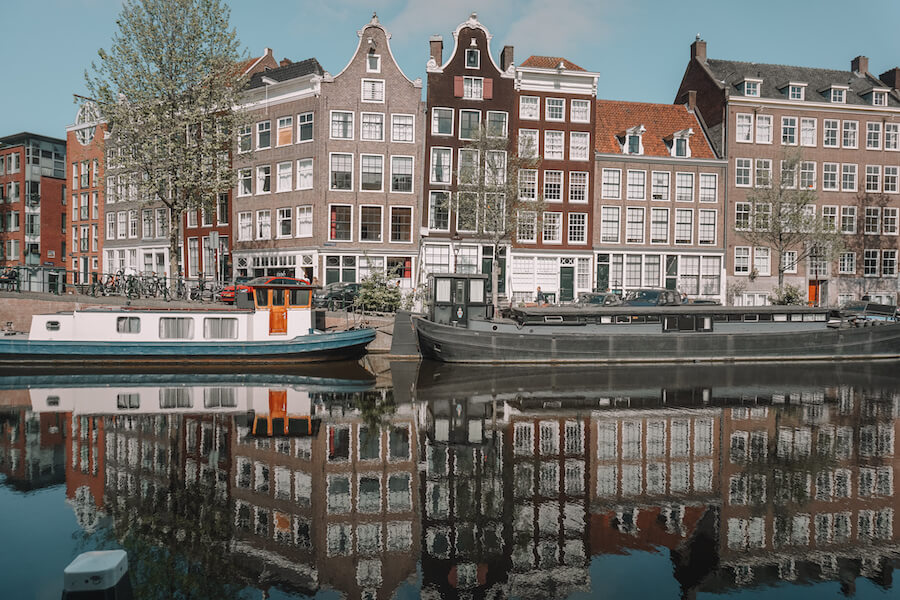 Canal in Amsterdam with houses reflecting off the water