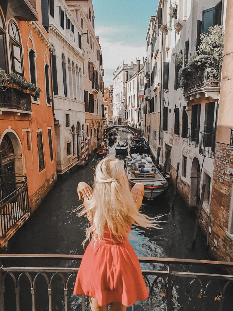 Girl standing infont of a canal in Venice, Italy