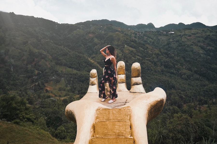beautiful places in Cebu - girl standing on a hand overlooking the hilly landscape