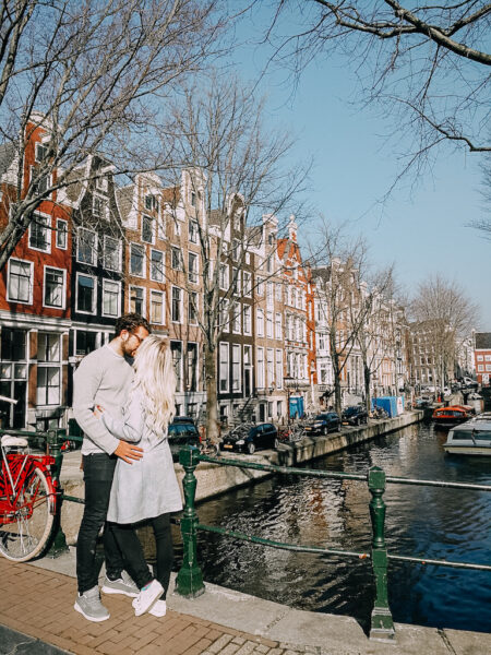 Two people standing on a canal in Amsterdam